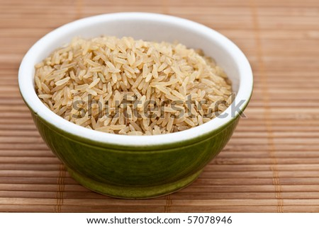 Brown rice in a green bowl on a bamboo mat