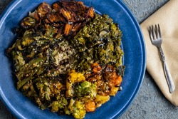 Brown Rice Plate with Roasted Veggies Including Rainbow Tomatoes, Orange Cauliflower, Romanesco Broccoli, Kale, and Asparagus on a Blue Plate