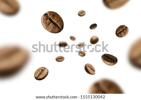 Brown roasted coffee beans falling and flying on black background.Represent breakfast for energy and freshness concept.