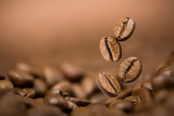 Brown roasted coffee beans falling on pile. Represent breakfast, energy, freshness or great aroma,Flying on dark background with copy space, close-up