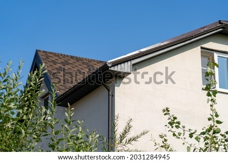 Brown roof of house covered with flexible bitumen motleysoft shingles under blue sky on sunny day. Cottage roof with metallic guttering system, guttering and drainage pipe exterior Photo stock ©
