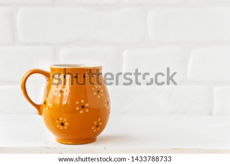 Brown rustic mug with flowers on white brick wall background. Copy space #1433788733