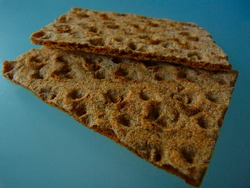 brown rustic thin rye crisp bread slice or cracker. rough textured grainy surface with bumps and holes on dark gray glass surface. healthy food concept. abstract closeup view. background image.
