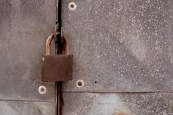 brown rusty old lock on metal doors