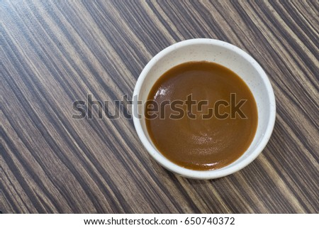 Brown sauce in white cup for seafood and barbecue  on wooden background   #650740372