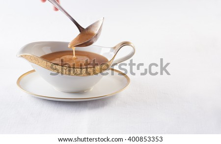 Brown sauce is poured into a spoon in a white gravy boat on a white tablecloth, horizontal Сток-фото ©