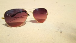 Brown shade sunglasses with golden metallic frame placed on soil in desert with copy space