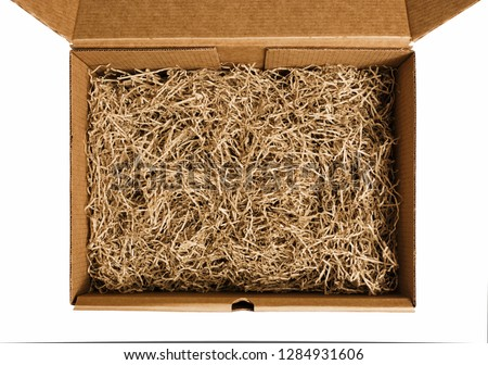 Brown shredded paper for gifting and stuffing in cardboard box. Top view.