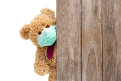 Brown sick teddy bear with protective medical mask behind the old wooden door or window. Stay at home quarantine coronavirus pandemic prevention, covid-19 concept.