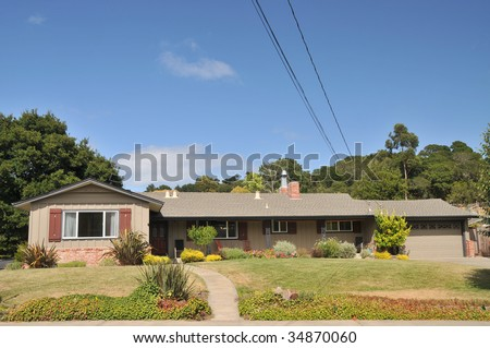 Brown single family house with grass in front has wires and cables coming off the roof