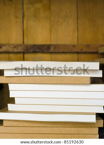 Brown sketch book stacked on wood shelf