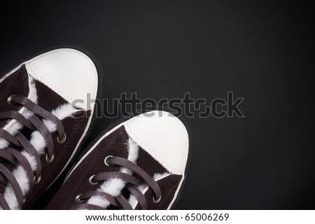 brown sneakers at black background