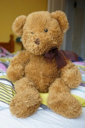 Brown soft teddybear sitting on a bed