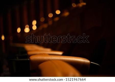 brown special leather seat in movie theater. pattern of many armchairs in dark room .