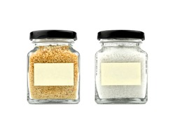 Brown sugar and salt in a glass jar with black lid and empty sticky note paper isolated on white background, front view.