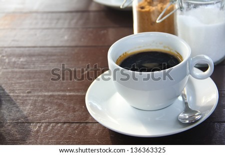 brown sugar and white sugar a cup of coffee on table
