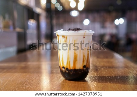 Brown sugar bubble drink. A plastic cup of fresh milk and brown sugar boba/bubble toppings and topped with chocolate cookies on wooden table.
