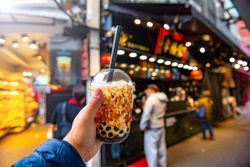 Brown sugar bubble milk tea or tiger brown sugar milk tea on a plastic cup with hand holding up, blurry background.