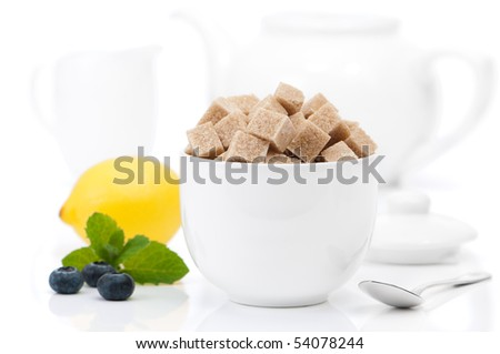 Brown sugar cubes in bowl with teapot and milk jug in background