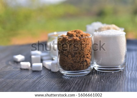 Brown sugar in clear glass with glass of granulation sugar and cube sugar background