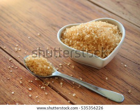Brown sugar in heart bowl shape on wood table.