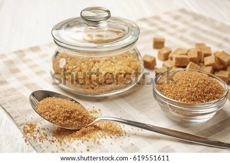 Brown sugar in spoon and dishware on napkin