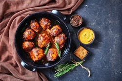Brown Sugar Mustard Chicken thighs in a baking dish on a concrete table with brown cloth and ingredients, horizontal view from above, flat lay, free space