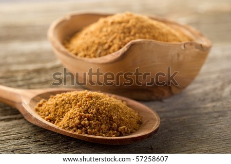 brown sugar over spoon on wood background