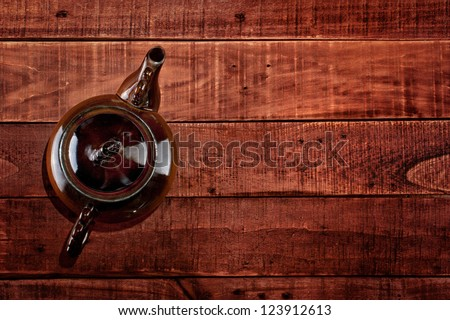 Brown teapot on the wooden table, top view