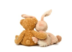 brown teddy bear and cute rabbit sit on white isolated background, toys sit with their backs hugging