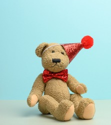 brown teddy bear in a red cap sits on a blue background, close up