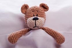 brown teddy bear lyiing sick in bed