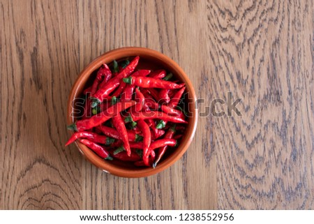 brown terracotta bowl full of red chillies to be dried. Bowl of spicy chili peppers Mexican type du a kitchen table, spicy spices for cooking