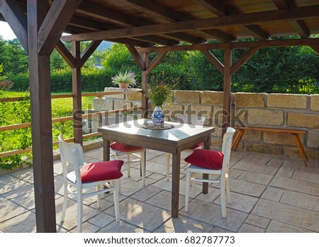 brown tiber wooden gazebo - pergola with table and chairs with red pillows with sandstone wall and floor pavement with summer flowers in the garden #682787773