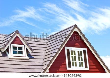 Brown tile roof in garden against blue sky.