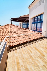 Brown tiled roof near large terrace with shiny metal railing in hotel at luxury tropical resort under blue sky on summer day