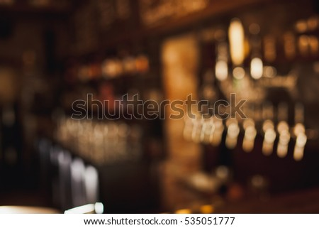 Brown toned bar out of focus blurred background with beer cranes and menu on chalkboard