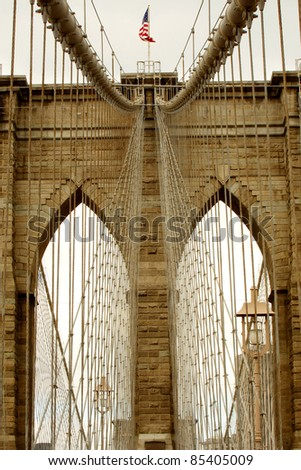 brown toned detail photo of Brooklyn Bridge in New York City, waving American flag