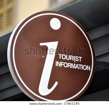 Brown tourist information sign mounted on the facade of a building
