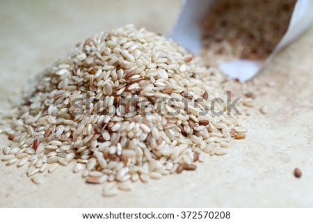 Brown uncooked rice in small sack on the table #372570208