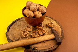 brown walnuts along with hammer on a wooden desk and yellow-brown background