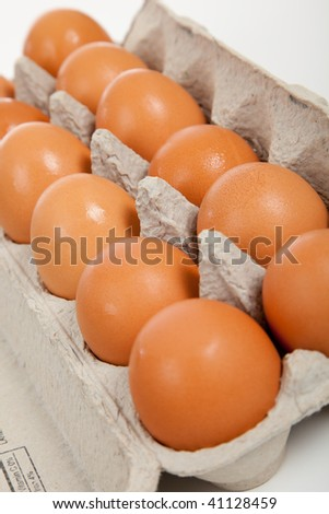 Brown whole eggs in a carton on a white background