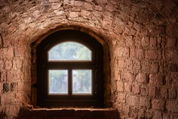 Brown window with an arch in a recess in the wall made of old red brick. From the window of the world series.
