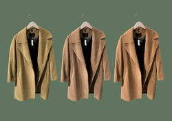 Brown women coat on hangers isolated on green background. Composition of clothes. Flat lay, top view, copy space. Ladies' Trench Coat. Winter clothes pattern. Strict classic brown coat