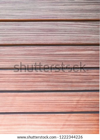 Brown wood wall with grooves between each sheet of wood.