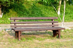 Brown wooden bench in the park. Summer sunny day. Green grass and trees. Resting and relaxing area. Empty bench for sitting. Wood exterior material.