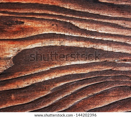 Brown wooden board close-up. Dark wooden background.