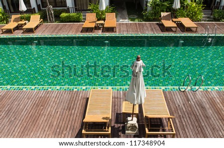 Brown wooden chairs side swimming pool.