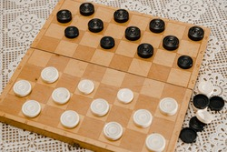 Brown wooden chessboard with classic checkers. Table game. Checkers on playing field for the game.
