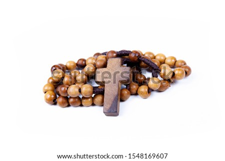 Brown wooden christian rosary curled up, christianity religious symbols isolated on white. Cross symbol in the middle. Chaplet of Divine Mercy prayer conept. Faith, belief. Studio shot #1548169607
